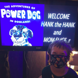 """Hank Crozier stands in our studio wearing a mask and smiling in front of a screen with our cover art and the words """"Welcome Hank the Hank and Mom Slice!"""""""
